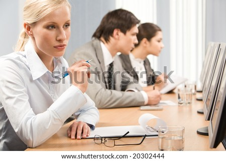 Confident business lady looking at display of computer while planning work
