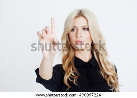 Confident business lady, touching finger to screen, touching digital screen with finger, place for your text or design. Focus on hand