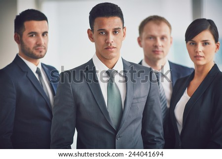 Confident business leader and his team looking at camera - stock photo