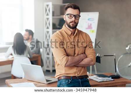 Confident business leader. Confident young man keeping arms crossed and looking at camera while his colleagues working in the background - stock photo