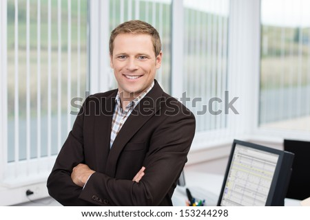 Confident business leader or manager standing leaning against his desk at the office with his arms folded smiling at the camera - stock photo