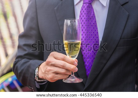 confident business man holding a glass of champagne. - stock photo