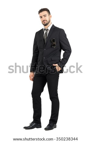 Confident business man in suit with sunglasses in pocket looking at camera. Full body length portrait isolated over white studio background.