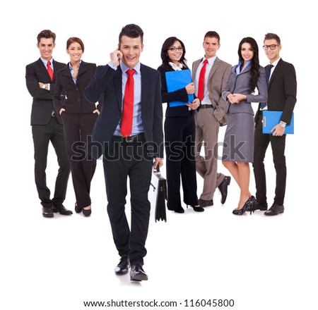 confident business man leader walking forward , while talking on the phone in front of his team