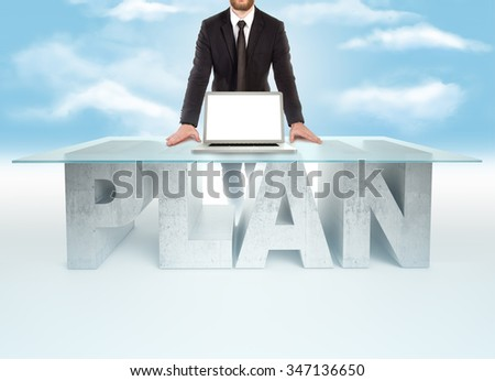 Confident business man leaning on PLAN table with open laptop - stock photo