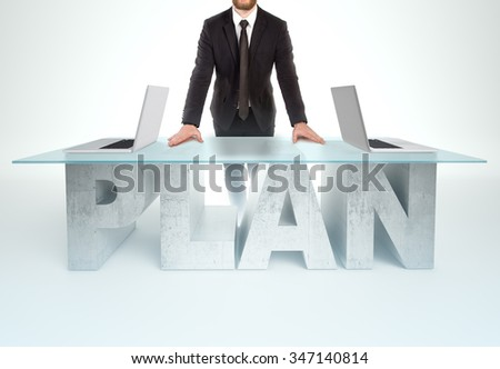 Confident business man leaning on PLAN table with open laptops Bussines concept - stock photo