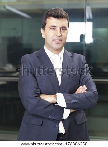 Confident business man standing with arms crossed at the office - stock photo