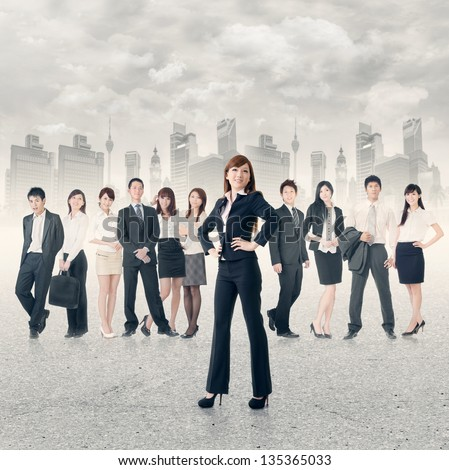 Confident business manager with her business team stand on road in modern city.