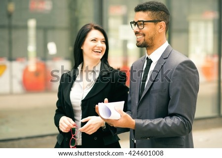 Confident business partners walking down in office building and talking with smile on their face - stock photo