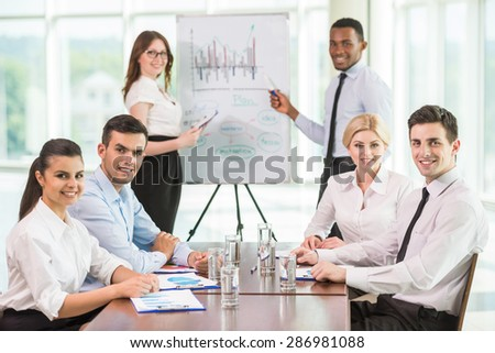 Confident business people commenting marketing results to colleagues at meeting. - stock photo