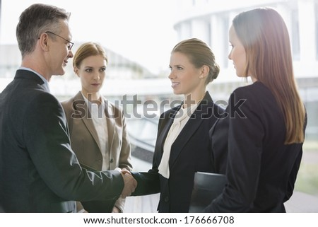 Confident business people shaking hands at workplace - stock photo