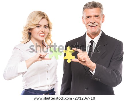 Confident business people wanting to put two pieces of puzzle together. Business solution concept. - stock photo