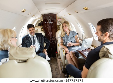 Confident business professionals having drinks on a private jet - stock photo