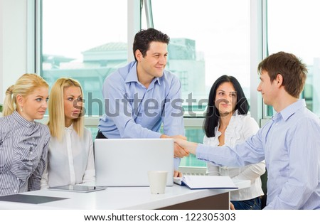 Confident business team leader congratulating after the presentation while the rest of the team watching with envy