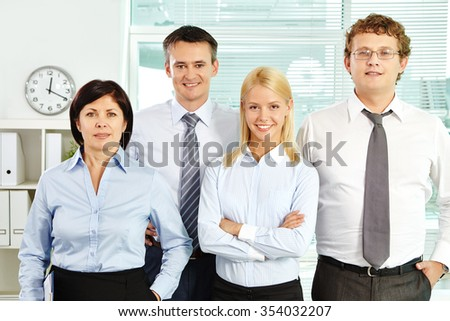 Confident business team looking at camera in office