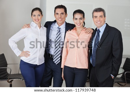 Confident business team smiling in the office - stock photo