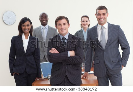 Confident business team standing in a meeting and smiling at the camera - stock photo