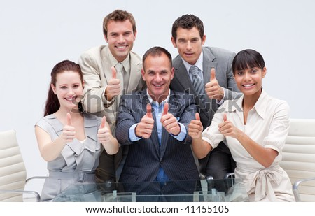 Confident business team with thumbs up in the office