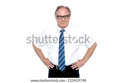 Confident business tycoon striking a pose with hands on his waist. - stock photo