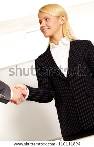 Confident business woman congratulating a business partner and shaking hand with him - stock photo