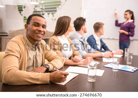 Confident business woman in meeting at office with team.