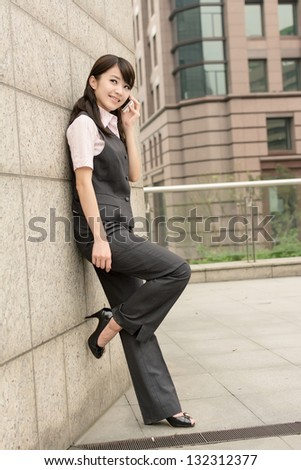 Confident business woman lean against wall and talk on cellphone in city.