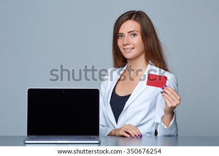 Confident business woman showing blank black laptop computer screen and blank credit card, sitting at table over gray background. - stock photo