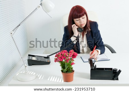 Confident business woman speaks by phone and writes in notebook - stock photo