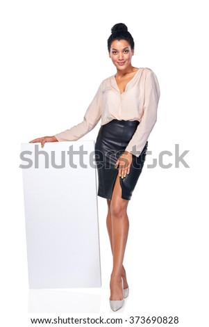 Confident business woman standing leaning at blank white banner in full length, over white background - stock photo
