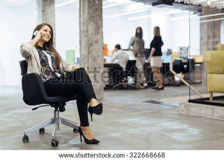 Confident business woman using phone in an office - stock photo