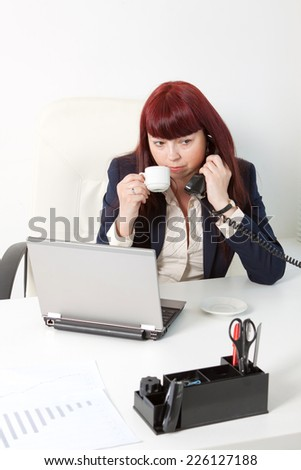 Confident business woman works and drinks coffee - stock photo