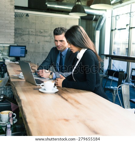 Confident businessman and attractive businesswoman using laptop in cafe - stock photo