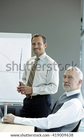 Confident businessman and his partners discussing growing graphs on a whiteboard - stock photo