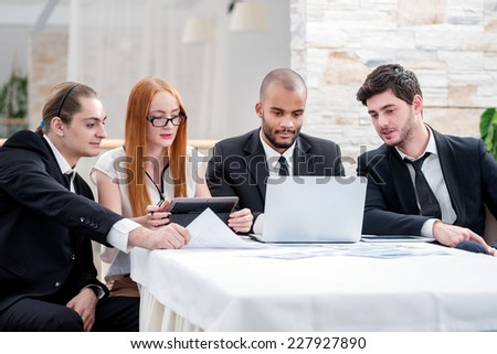 Confident businessman at a meeting. Four smiling successful businessmen sitting at table in office while discussing their business doings. Young people talking in office