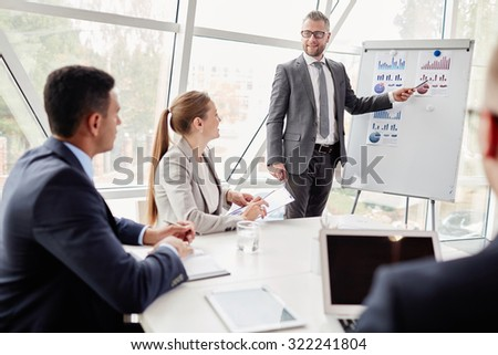 Confident businessman by whiteboard showing data upon sales on the market to his colleagues - stock photo