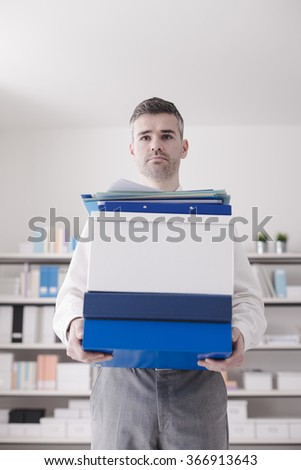Confident businessman carrying boxes and paperwork in the office
