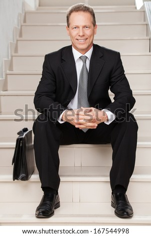 Confident businessman. Cheerful mature man in formalwear smiling at camera while sitting on staircase