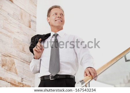 Confident businessman. Cheerful mature man in formalwear smiling while moving down by staircase  - stock photo