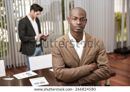Confident businessman. Cheerful young African man in formalwear keeping arms crossed and smiling while his caucasian colleague standing on background - stock photo