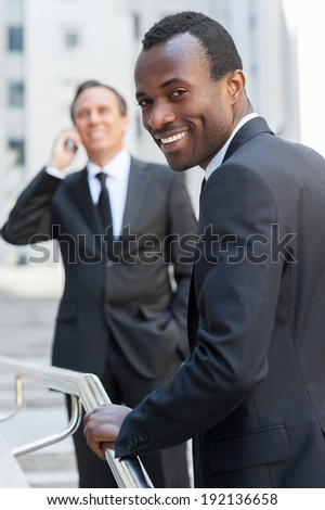 Confident businessman. Cheerful young African man in formalwear moving up by stairs and looking over shoulder while senior man talking on the mobile phone in background