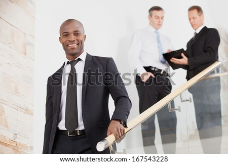 Confident businessman. Cheerful young black man in formalwear moving down by staircase and smiling while two people talking on background - stock photo