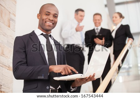 Confident businessman. Cheerful young black man in formalwear standing on staircase and holding a laptop while three people talking on background - stock photo