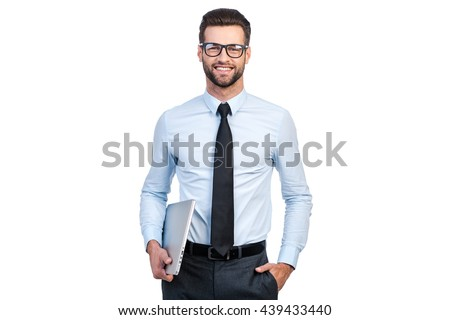 Confident businessman. Confident young handsome man in shirt and tie carrying laptop and looking at camera with smile while standing against white background - stock photo
