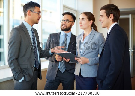 Confident businessman explaining his idea to female and male partners in office - stock photo