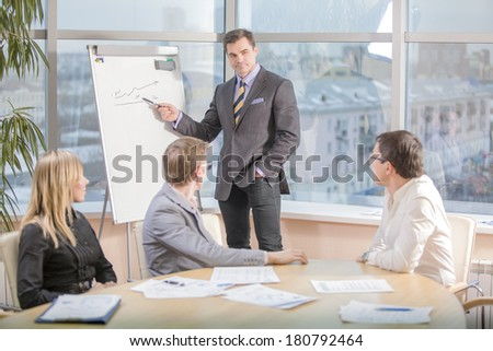 Confident businessman explaining something to colleagues at meeting - stock photo