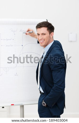 Confident businessman giving a presentation as he stands in front of a flip chart drawing a graph and turning to smile at the camera - stock photo