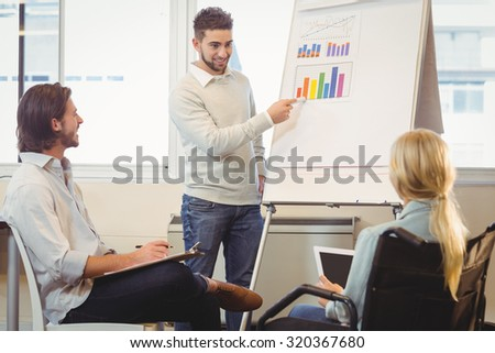 Confident businessman giving presentation as colleagues looking at it during meeting in creative office