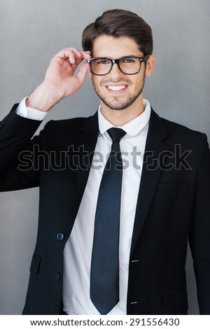 Confident businessman. Handsome young man in formalwear adjusting his eyeglasses and smiling while standing against grey background - stock photo