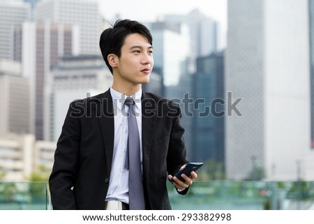 Confident businessman hold with smartphone - stock photo