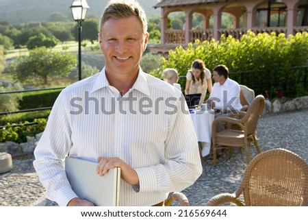 Confident businessman holding laptop at caf�½ with coworkers in background - stock photo